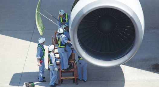 Aircraft maintenance workers servicing airplane engine
